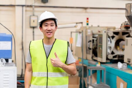 Front view of Asian factory worker with safety hard hat posed looking at camera with happy smile in industrial facilities at heavy industry manufacturing factory. He is giving thumbs up for approval