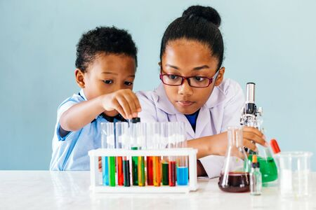 Two curious African American children conducting interesting chemistry experiments with colorful liquids while learning science in laboratory