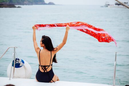 Back view of young brunette woman swinging bright red pareo sitting on yacht in calm sea