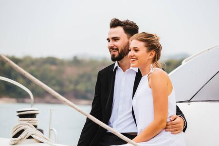 Handsome man and attractive woman embracing smiling on yacht in bright day