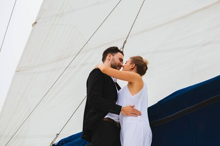 Handsome man and attractive woman smiling and kissing embracing on yacht in bright day Imagens