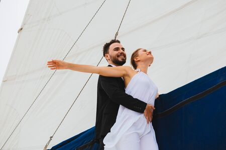 Handsome man hugging attractive woman outstretching hands wide on yacht in bright day Stock fotó