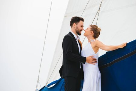 Handsome man and attractive woman smiling and kissing embracing on yacht in bright day Stock fotó