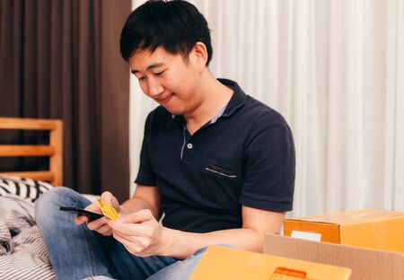 Adult Asian male smiling and using online banking service with smartphone and credit card for shopping while sitting near delivery boxes Banque d'images - 126635547