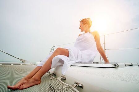 One young beautiful Caucasian woman smiling and looking away on yacht sailboat with ocean sea in background. She is sitting and wearing white summer dress.