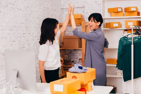 Side view of cheerful Asian entrepreneurs doing high five while working in office of online fashion business company