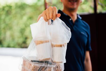 Close-up of male food delivery man on service job giving foods of bubble tea, coffee, lunch box at home Foto de archivo