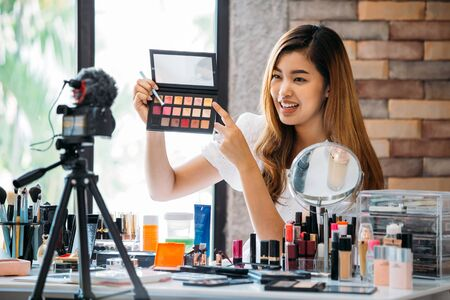 Pretty Asian woman sitting at table and making video about cosmetics while filming with camera on tripod Stock Photo