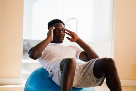 Young African American man doing sit-up exercise with swiss ball at gym. Male fitness model performing a crunch at fitness center Stock Photo