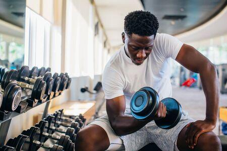 Junge Afroamerikaner sitzen und heben eine Hantel in der Nähe des Racks im Fitnessstudio. Männliche Krafttrainingsperson, die einen Bizepscurl im Fitnesscenter macht Standard-Bild