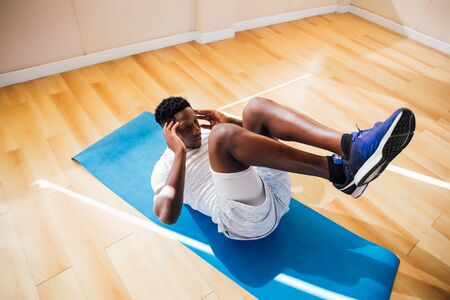 Top view of young African American man doing sit-up exercise on yoga mat at gym. Male fitness model performing crunch at fitness center