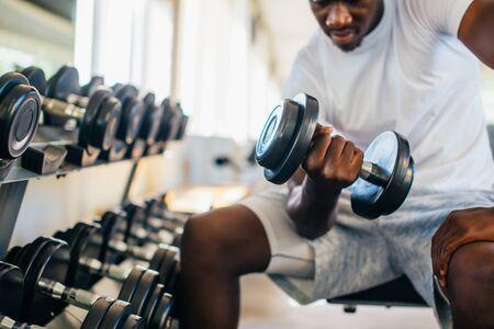 Joven afroamericano sentado y levantando una pesa cerca de la rejilla en el gimnasio. Persona de entrenamiento con pesas masculino haciendo un curl de bíceps en el gimnasio Foto de archivo