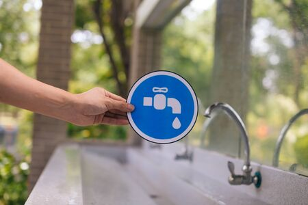 Male hands holding a blue faucet sign with the tap water faucet in the park. Save water and environmental concern concept Stock Photo