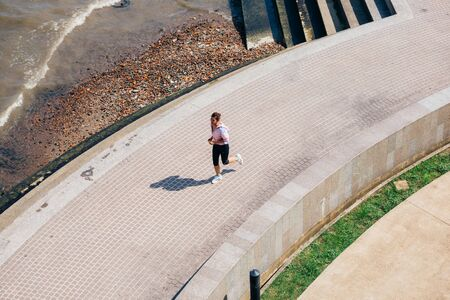 From above Asian woman in sportswear running along paved path near waving sea during outdoor training on sunny day Stok Fotoğraf