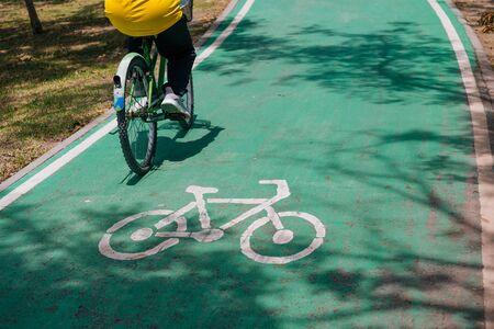 Unrecognizable biker cycling on green bike lane during summer. Green transportation