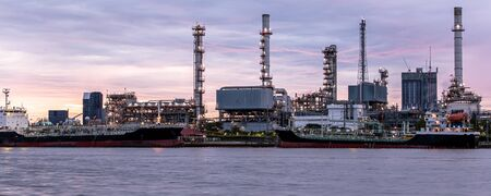petroleum oil refinery plant beside river in twilight time. Crude Oil Process machinery