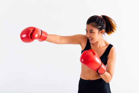 Portrait of a young smiling female boxer punching on white isolated background with copy space. Asian woman doing boxing exercise with happy look.