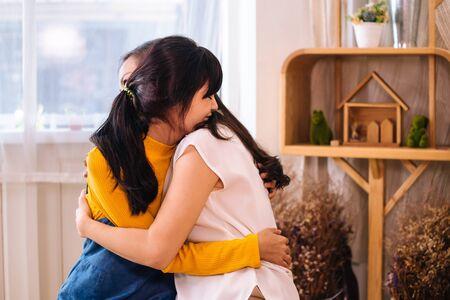 Gezicht van lachende Aziatische tienerdochter en Aziatische moeder van middelbare leeftijd knuffelen met gelukkige warme uitdrukking en tederheid in de woonkamer binnenshuis. Ze hebben een goede relatie met elkaar.