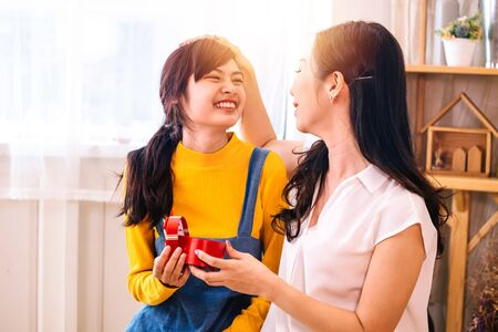 Asian middle-aged mother touching Smiling happy Asian teenage daughter in indoor living room at home. Mum holds and opens a present gift.