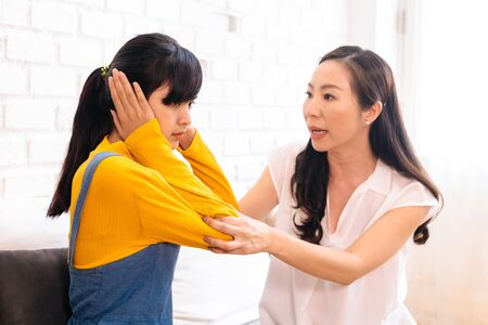 Argument between annoyed Asian teenage daughter and upset middle aged mother. The child covering ears while mum arguing. Bad, unhealthy, toxic family relationship concept