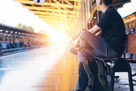Young Asian male travel backpacker sitting and waiting for a train in railway platform in Bangkok, Thailand - Asia Travel tourism concept