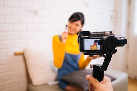 Young Asian woman holding cosmetics brush while recording a video with professional camera. Beauty vlog blogging and internet influencer business concept Stock Photo