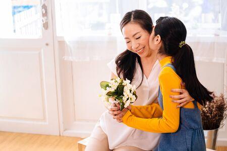 Volto di una figlia adolescente asiatica che abbraccia e bacia una madre di mezza età sorridente felice con tenerezza nel soggiorno al coperto a casa. La madre tiene in mano un bouquet ricevuto dal bambino. Concetto di festa della mamma