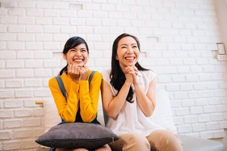 Cheerful Asian mother and daughter smiling while relaxing at home and watching TV on white brick wall background
