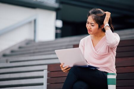 Young Asian girl having headache and scatching her head with laptop on her lap in university campus building. One woman stressed out outdoors Reklamní fotografie