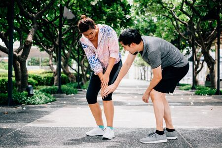 Asian male touching aching knee of woman in sportswear while helping during accident on training in park Banco de Imagens