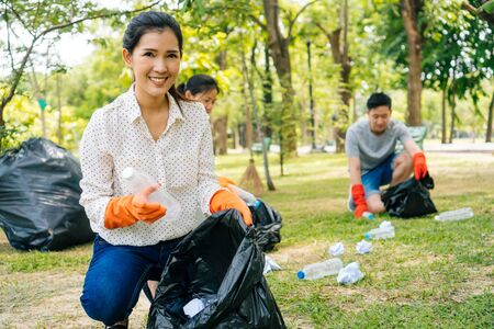 Young Asian woman and group of volunteers wearing orange gloves and collecting garbage in trash bin bag in the park. Save the earth and environmental concern concept