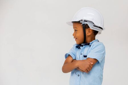 African American kid wearing hard helmet with arms crossed isolated on white background Archivio Fotografico - 128858984