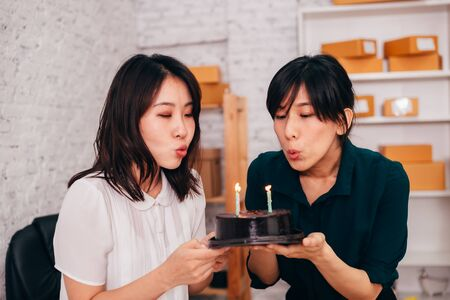 Cheerful Asian colleagues smiling and blowing candles on cake while celebrating birthday in office