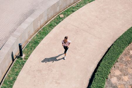 From above Asian female in sportswear running along concrete path in park during outdoor workout on sunny day