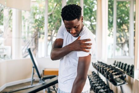 Side view of muscular African American man standing and suffering from shoulder pain during workout with dumbbells. Sportsman holding sore shoulder in gym