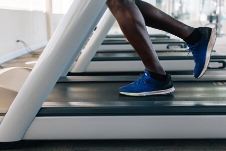 Side view of African American sportsman in blue sneakers working out on electric treadmill in fitness club. Faceless male runner running on treadmill Banco de Imagens