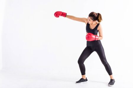 Strong Asian woman in black sportswear and red boxing gloves punching isolated on white background with copy space. Young fit female doing boxing exercise Banco de Imagens