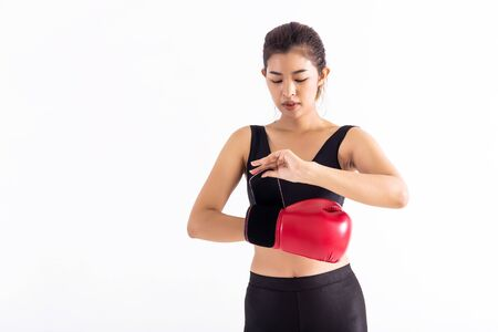 Fit Asian woman putting on red boxing gloves before boxing workout on white background. Young sportswoman fixing on hand red leather glove. Stock Photo