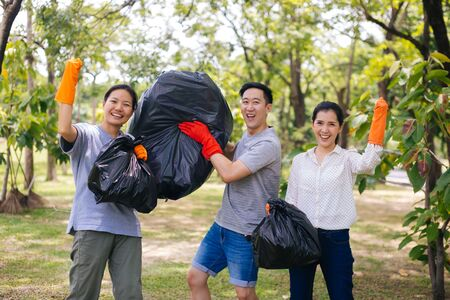 Voluntary man and women collecting trash for saving nature and smiling with raised hands in park holding filled plastic bag Banco de Imagens - 128859650
