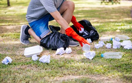 Cropped casual man in red gloves collecting garbage in park for social contribution on summer day
