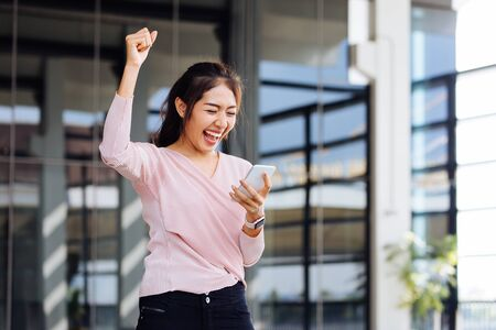 Cheerful Asian woman fist up getting good news from mobile phone in hand