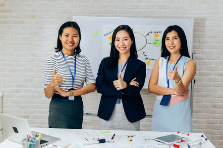 Smiling Asian young business women in casual wear standing in line with thumbs up gesture in meeting room. Row of Business men and women looking at camera 版權商用圖片