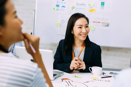 Asian mature business woman smiling and looking at other business people while sitting in meeting. Smart middle age lady having discussion.