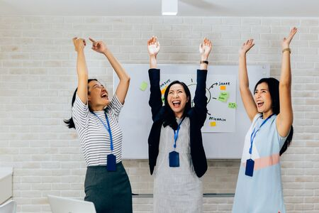Smiling Asian young and mature business women standing in line with arms raised up gesture in meeting room with excited feeling. Row of Business people portrait 写真素材