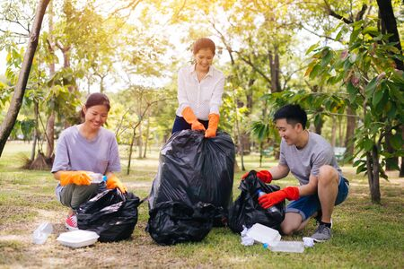 Young Asian man and women wearing orange gloves and collecting trash in garbage bag in the park. Save the earth and environmental concern concept