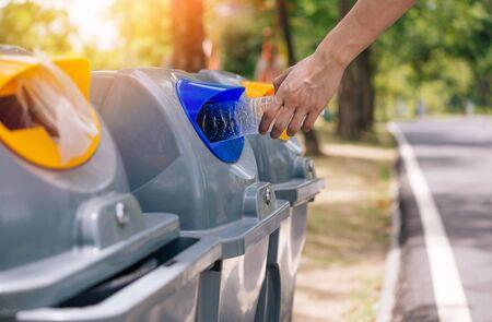 Primo piano della mano dell'uomo che getta una bottiglia di plastica nel cestino della spazzatura. Smistamento dei rifiuti prima di mettere nel bidone della spazzatura. Salva la terra e il concetto di preoccupazione ambientale Archivio Fotografico