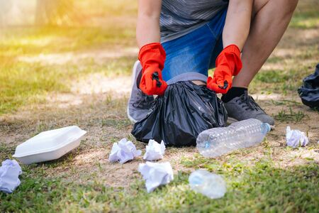 Young man wearing orange gloves and collecting trash in garbage bag in the park. Save the earth and environmental concern concept