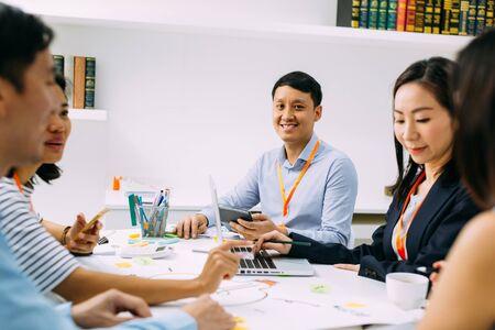 Asiatischer reifer Geschäftsmann, der die Kamera lächelt und betrachtet, während er beim Treffen mit anderen Geschäftsleuten und -frauen sitzt. Intelligenter Mann mittleren Alters, der eine Diskussion führt. Standard-Bild