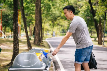 Close up of man hand throwing a plastic bottle into recycle dustbin. Garbage sorting before putting in garbage bin. Save the earth and Environmental concern concept 免版税图像