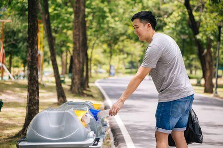 Primo piano della mano dell'uomo che getta una bottiglia di plastica nel cestino della spazzatura. Smistamento dei rifiuti prima di mettere nel bidone della spazzatura. Salva la terra e il concetto di preoccupazione ambientale